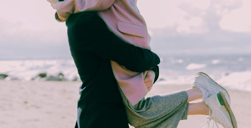 man-in-gray-coat-carrying-woman-wearing-pink-coat-in-beach-698885